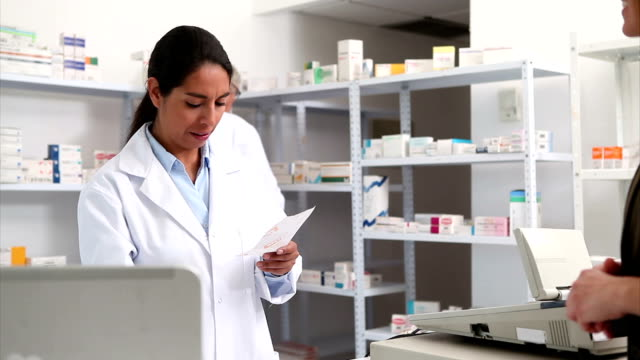 Smiling pharmacist handing paper to a customer video