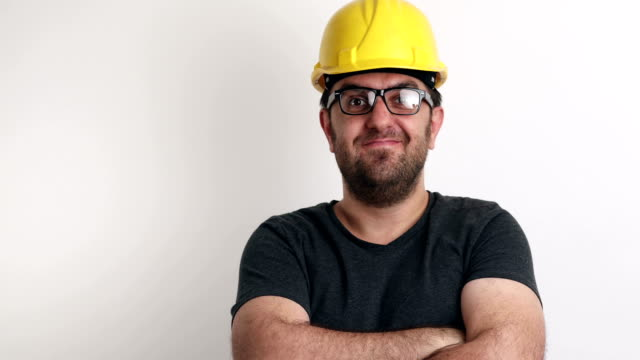 Smiling portrait of construction worker on white background video