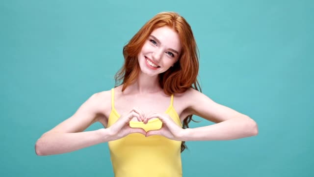 Smiling redhead girl making heart gesture infront of her chest and laughing isolated over blue background video