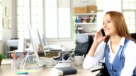 Smiling redhead woman talking on smart phone in modern office video