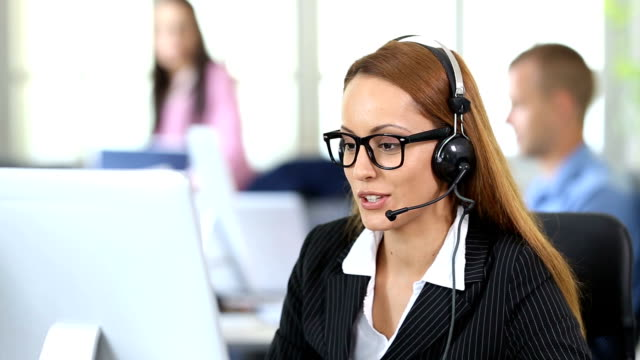 HD Smiling redhead woman with headset and eyeglasses using computer in modern office video