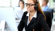 HD Smiling redhead woman with headset and eyeglasses working in modern office video