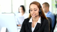 HD Smiling redhead woman with headset talking on smart phone in modern office video