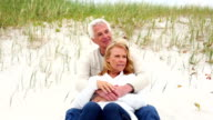 Smiling retired couple sitting on the beach video