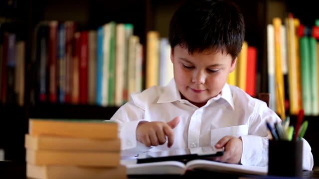 smiling school boy using digital tablet video