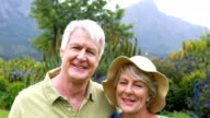 Smiling senior couple standing together in garden video