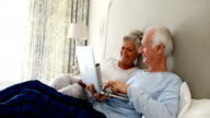 Smiling senior couple using laptop on bed in bedroom video