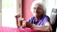 Smiling Senior Woman Stirring Hot Tea video