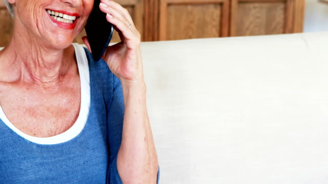 Smiling senior woman talking on mobile phone in living room video