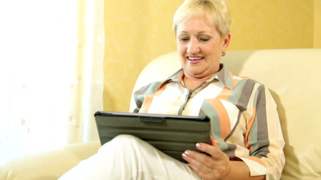 Smiling Senior Woman Using Digital Tablet video