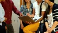 Smiling students using laptop in locker room video