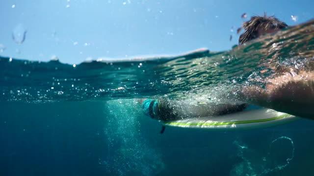 SLOW MOTION UNDERWATER: Smiling surfer man paddling on a surf in vast blue sea video