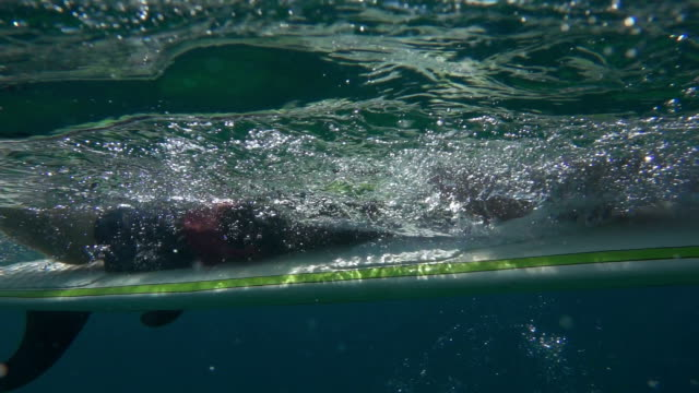 SLOW MOTION OVER-UNDER: Smiling surfer man paddling on surf in open water ocean video