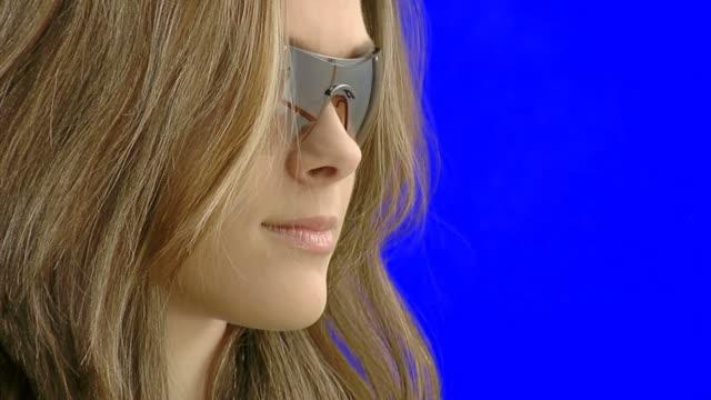 Smiling teen girl in sun glasses - studio shot video