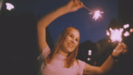 Smiling teenage girl on the street at night with sparklers video