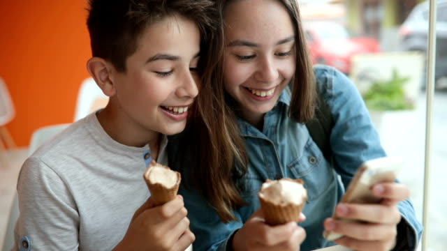 Smiling teens use smart phone video