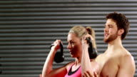 Smiling trainer helping woman lifting kettlebells video