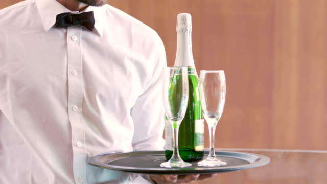 Smiling waiter holding champagne bottle and flute video
