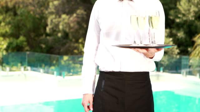 Smiling waiter holding champagne glasses video