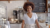 Smiling waitress behind counter at a coffee shop, close up video