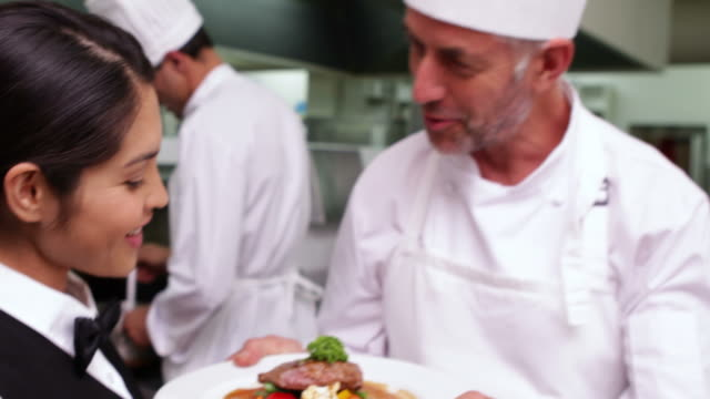Smiling waitress being handed a dish by chef video
