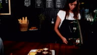 Smiling waitress offering coffee to pretty customer video
