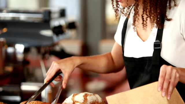 Smiling waitress picking rolls with tongs video