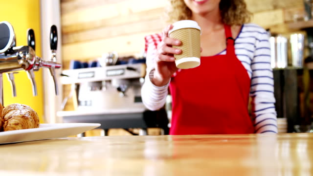 Smiling waitress serving a coffee at counter video