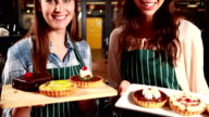 Smiling waitresses showing cakes video