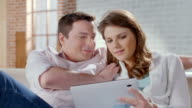 Smiling wife husband shopping online, choosing items on tablet video