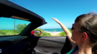 SLOW MOTION: Smiling woman driving along the coast playing with wind in summer video
