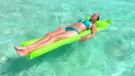 SLOW MOTION CLOSE UP: Smiling woman in bikini laying and tanning on air bed raft floatie on turquoise ocean water surface in Pacific island paradise video