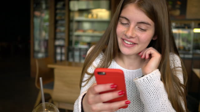 Smiling woman in cafe text messaging video