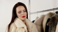 Smiling woman in fur jacket in front of clothing rack with fur coats video