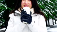 Smiling woman in warm clothing having coffee during snowfall video