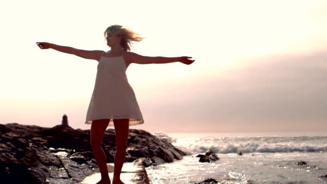 Smiling woman in white dress turning round video