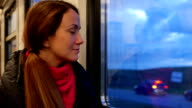 Smiling woman look out train window, railway trip video