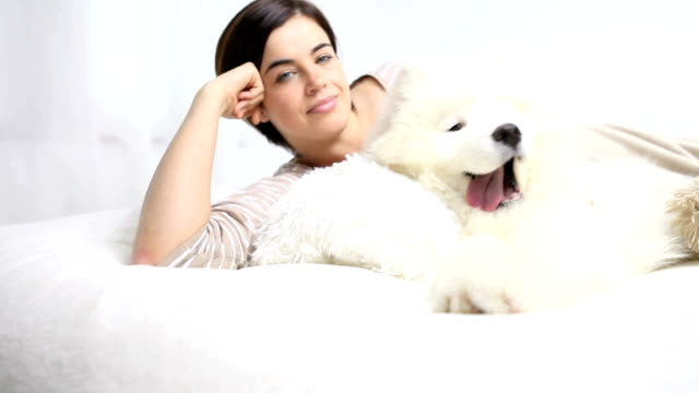 Smiling woman play with pet dog video