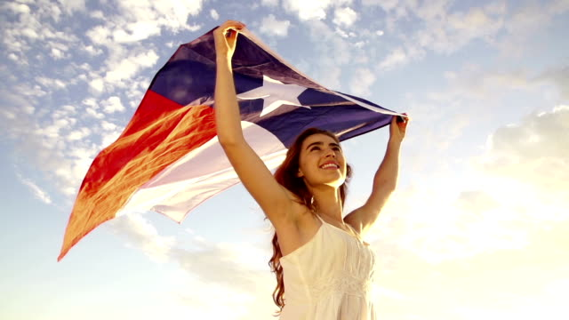 Smiling Woman proudly waving flag of texas in slow motion video