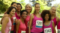Smiling woman racing pink for breast cancer awareness video