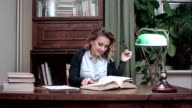 Smiling woman sitting at her desk and happily going through a book video