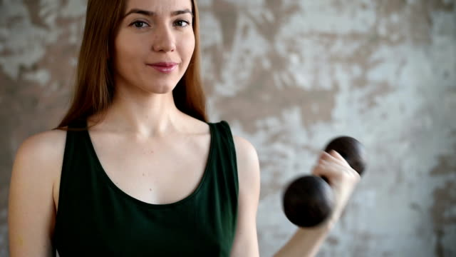 Smiling woman with a heavy dumbbell video