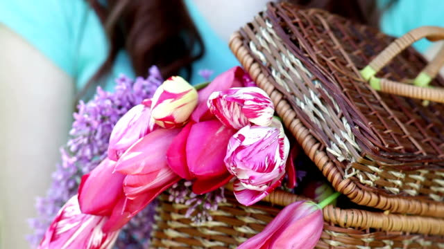 Smiling woman with bunch of tulips in basket video