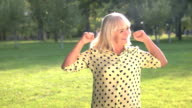 Smiling woman with raised fists. video