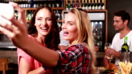 Smiling women taking selfie during a meal with friends video