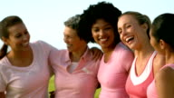 Smiling women wearing pink for breast cancer video