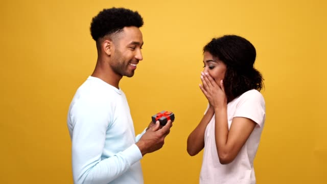 Smiling young african man giving a present box to his girlfriend isolated over yellow background video