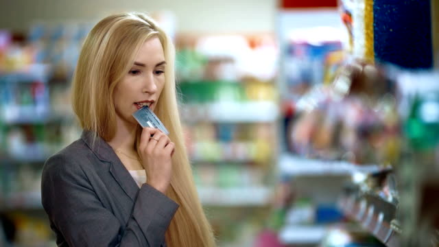 Smiling young casual woman with credit card hesitate in buying in supermarket video