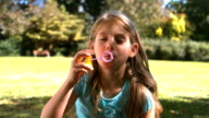 Smiling young girl blowing into a bubble wand video