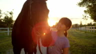 CLOSE UP: Smiling young girl petting beautiful big brown horse at golden sunset video